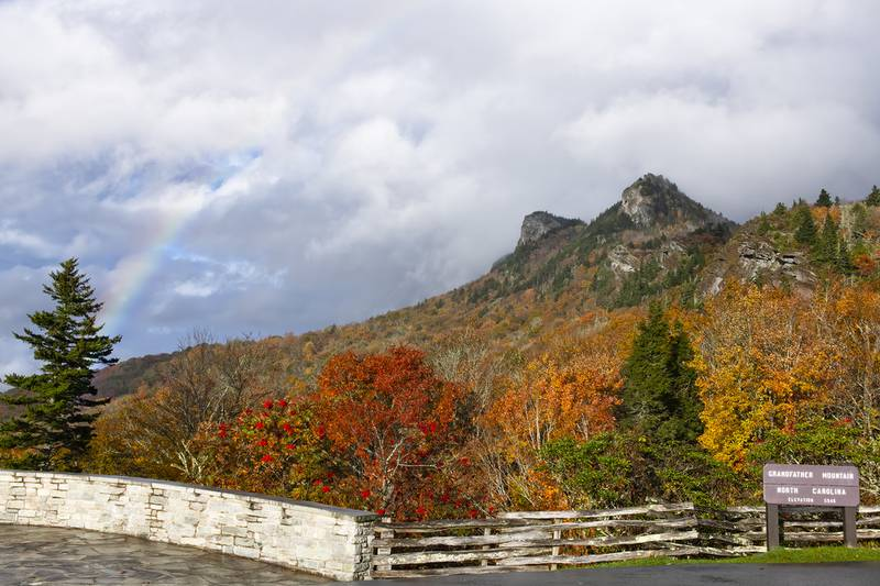 A rainbow forms over Grandfather Mountain's iconic peaks, as fall color brightens up the foreground at the park's Half Moon Overlook.