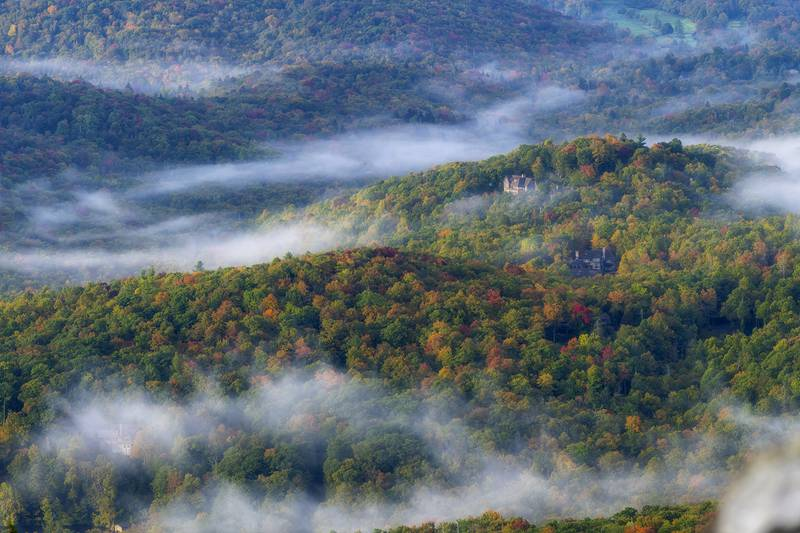 An early morning break in the clouds offers stunning views of color-dappled hills and valleys, as seen from atop Grandfather Mountain's Linville Peak and the Mile High Swinging Bridge.