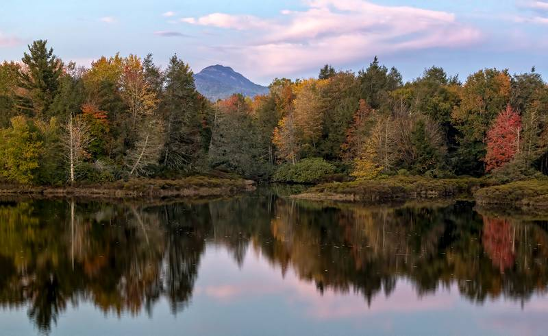 Fall color is reflected in the lake at Camp Yonahnoka near Linville, N.C., as Grandfather Mountain rises in the distance.