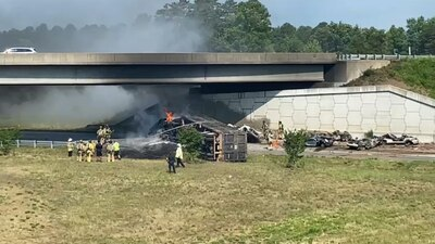 18-wheeler hauling crushed cars, flips, catches fire on busy interstate ramp